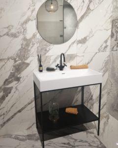 baño blanco y negro con azulejos de efecto mármol.